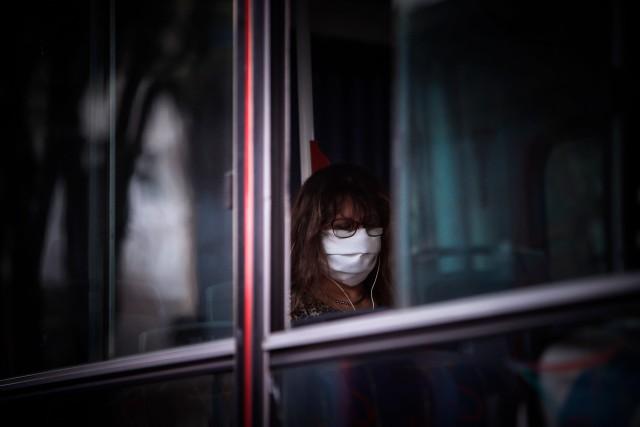 Una mujer con mascarilla usa un autobús público
